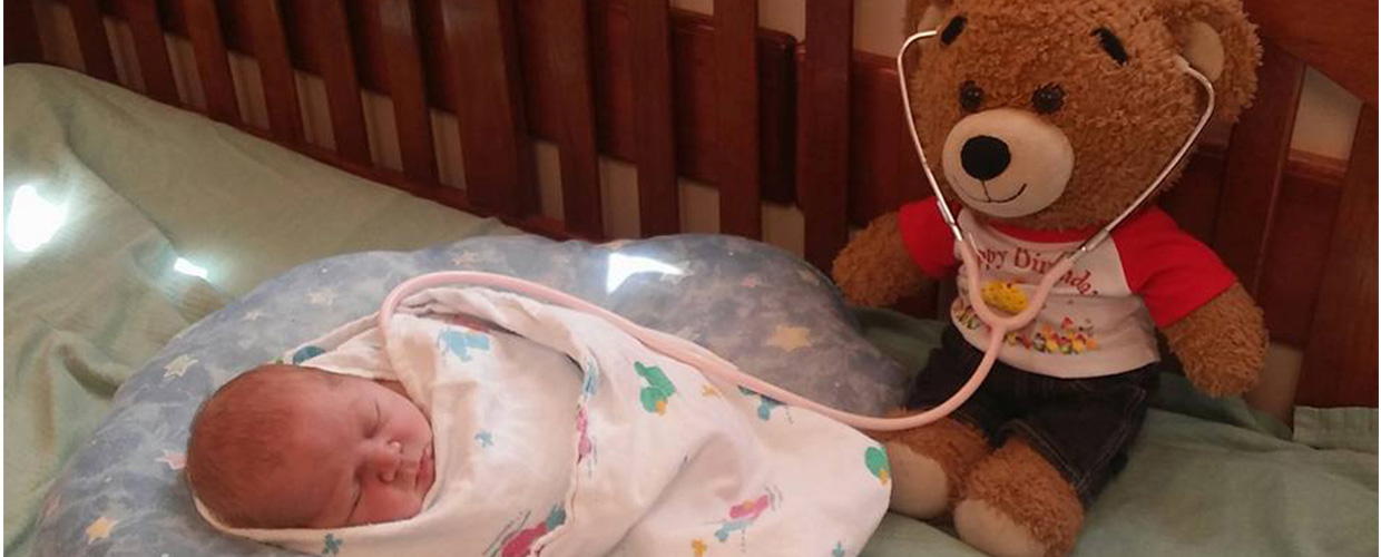 A teddy bear with a locket containing baby Preston's ashes sits alongside Krysten Bowen's young child Ryder