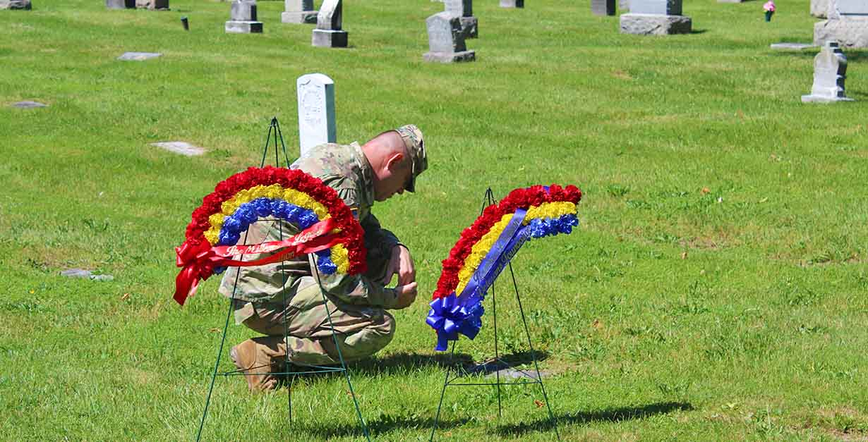 A member of the U.S. Military pays his respect at a grave site on Flag Day. St. Agnes Cemetery serves as the final resting place of hundeds of American veterans.