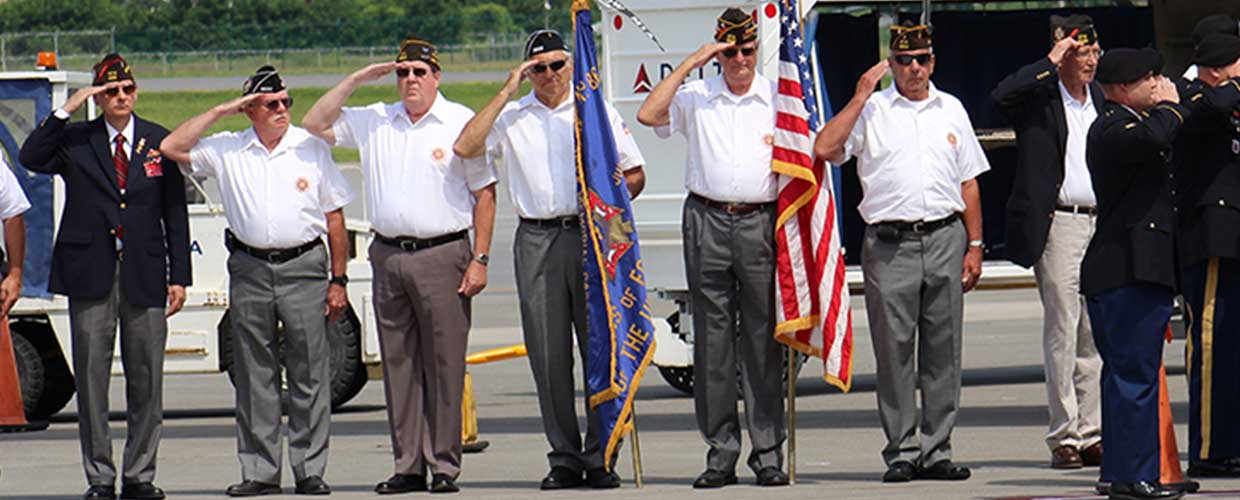 Veteran Service Organization Honor Guards Salute as Remains of a WWII Pilot are Offloaded from an Airplane