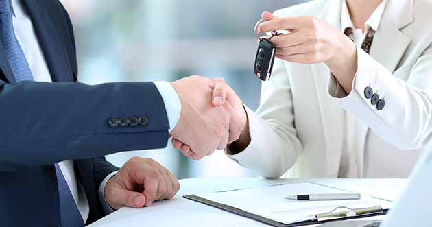 Handing keys to car over to auto buyer
