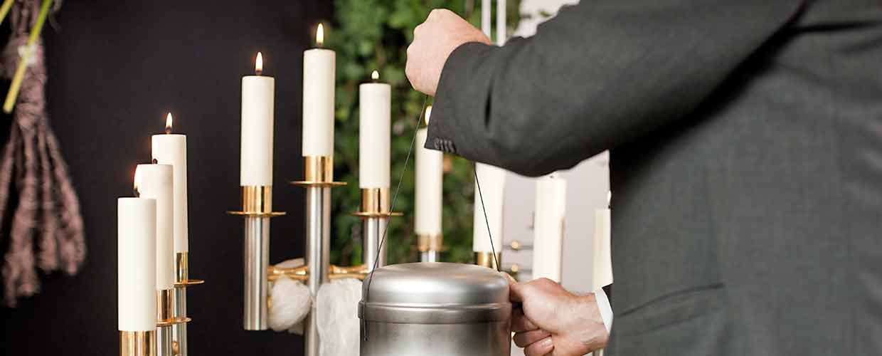 Funeral director lights candles surrounding a cremation urn