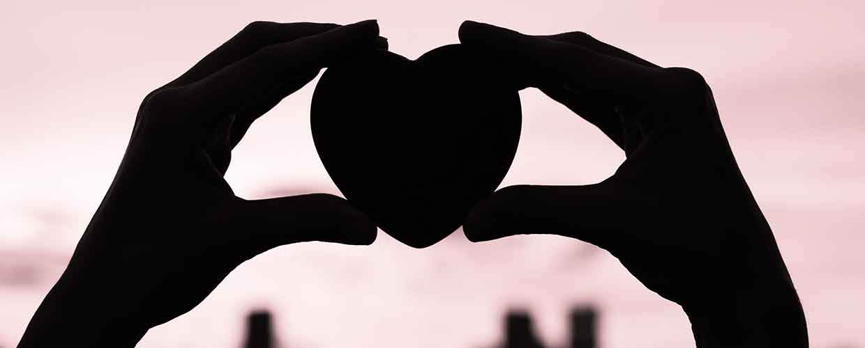 Silhouette of Heart shape held up against horizon